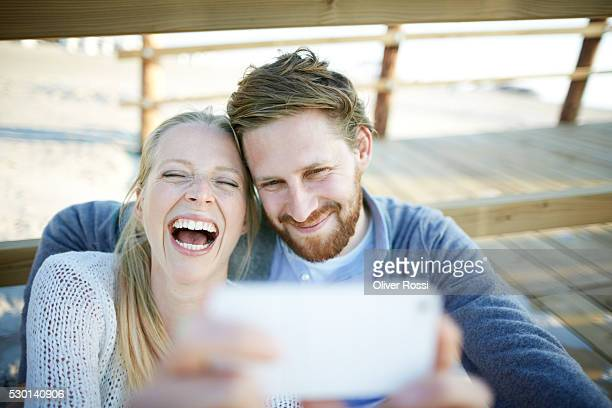 couple taking selfie on the beach - mid adult couple stock pictures, royalty-free photos & images