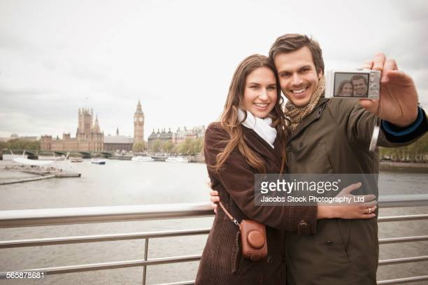 Couple taking selfie on urban bridge near city skyline, London, Middlesex, United Kingdom