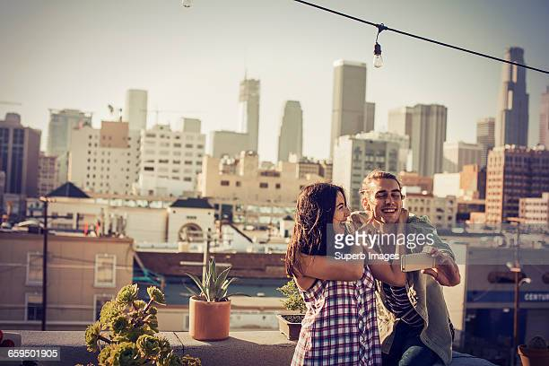 couple taking selfie on urban rooftop - brown hair stock pictures, royalty-free photos & images