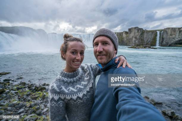 Couple taking selfie portrait with magnificent waterfall in Iceland, Godafoss falls. People travel exploration concept