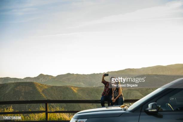 couple taking selfie while sitting on fence in countryside - road trip stock pictures, royalty-free photos & images