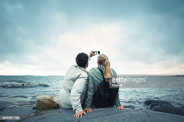 Couple taking selfie while sitting on rock by sea