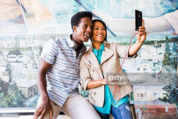Couple taking selfie with digital tablet by mural