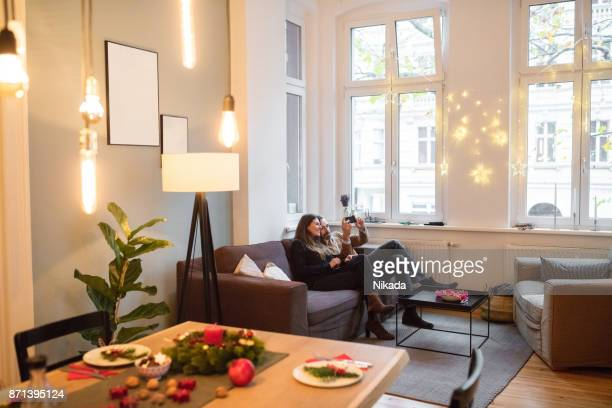 couple taking selfie with smartphone on sofa at home during christmas - illuminated stock pictures, royalty-free photos & images