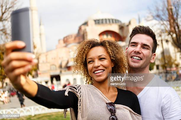 Couple taking selfies in front of Aya Sofya in Istanbul