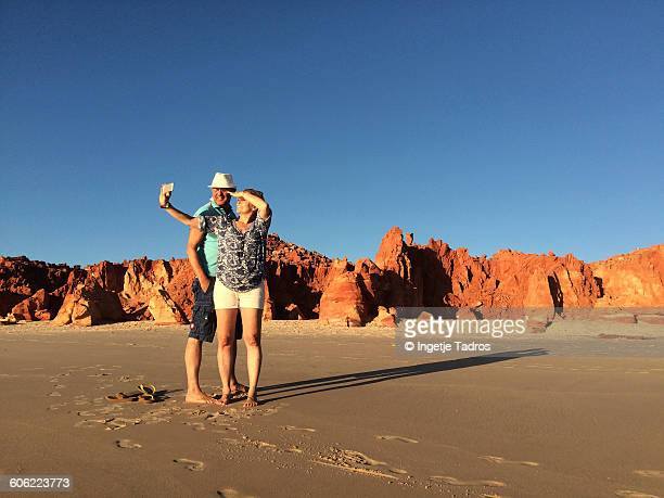 couple taking selfies on the beach at cape leveque - western australia stock photos and pictures
