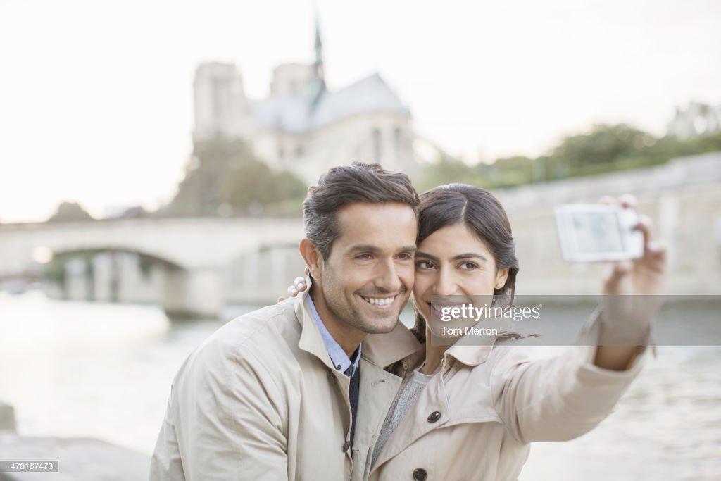 Couple taking self-portrait along Seine River near Notre Dame Cathedral, Paris, France : Stock Photo