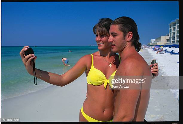 couple taking self-portrait on beach - panama city beach stock pictures, royalty-free photos & images
