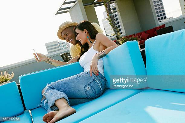 couple taking self-portrait on sofa on urban balcony - barefoot black men stock pictures, royalty-free photos & images