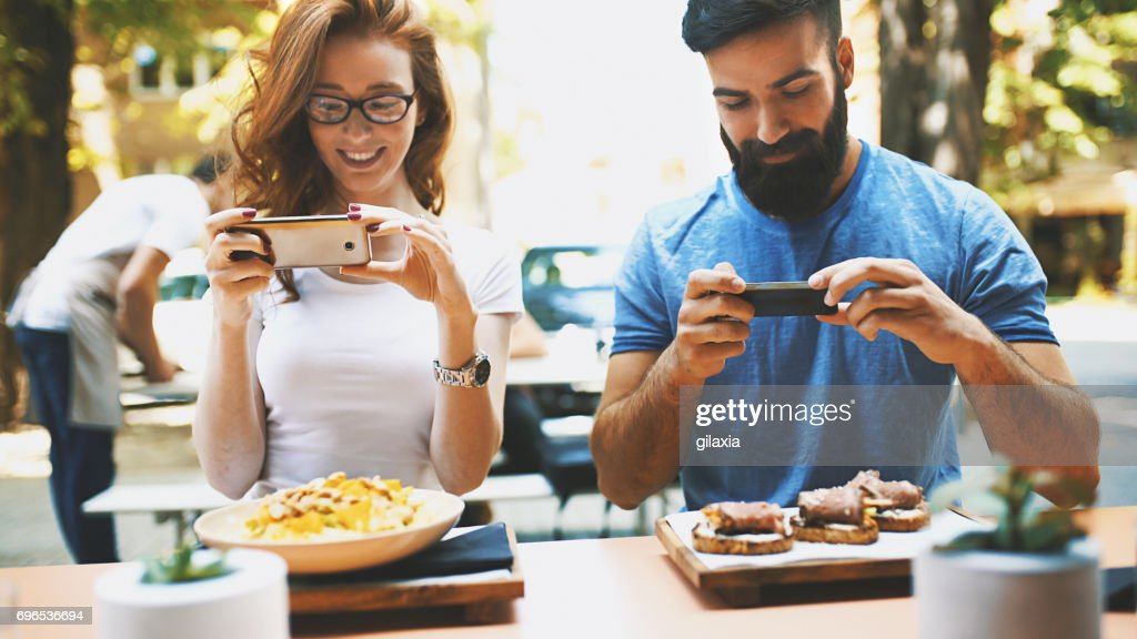 Couple taking shots of food. : Stock Photo