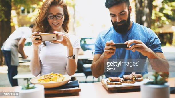 couple taking shots of food. - cibo pronto foto e immagini stock