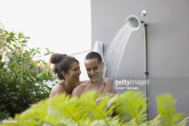 couple taking shower together outdoors - gigolo photos et images de collection