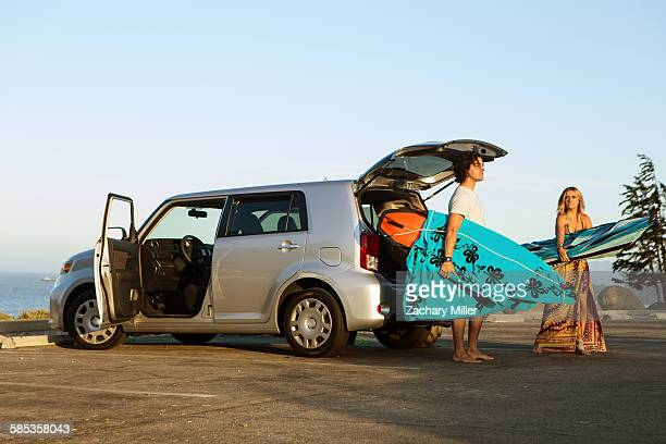 Couple taking surfboards from boot of car