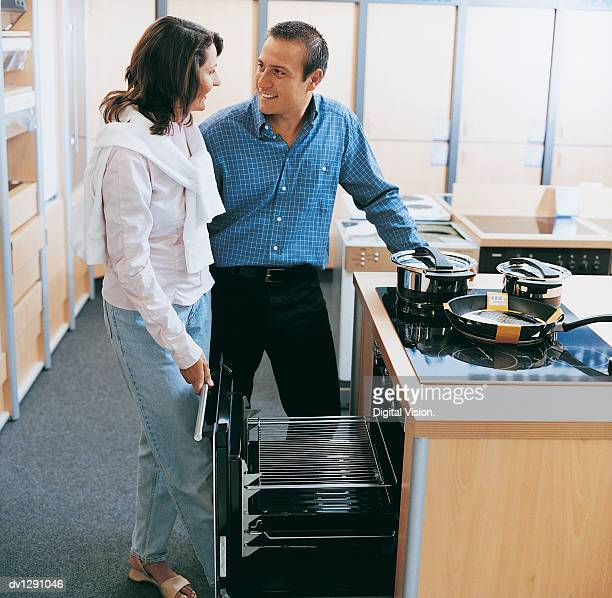 couple talking about an oven in a department store - electric stove burner stock pictures, royalty-free photos & images