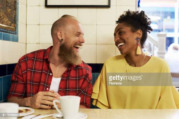 couple talking and laughing in a cafe - side by side stock photos and pictures