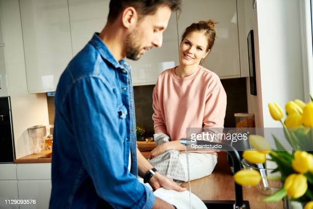 Couple talking and washing up in kitchen