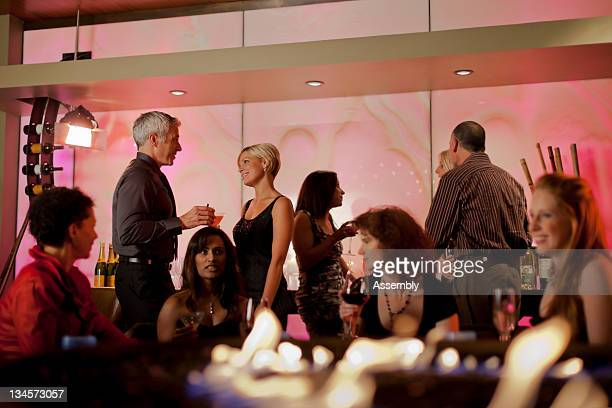 couple talking in a busy cocktail lounge. - cocktail party stock pictures, royalty-free photos & images