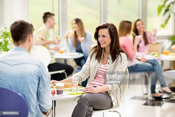 Couple talking in cafeteria.