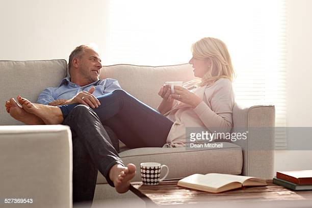 Paar in Unterhaltung im Wohnzimmer mit Kaffee