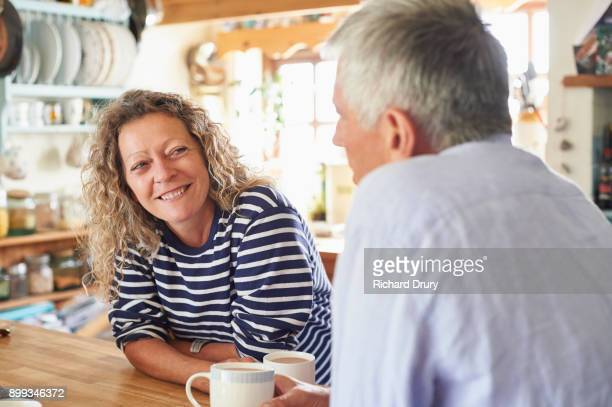 couple talking in their kitchen - 50 59 years stock pictures, royalty-free photos & images