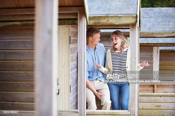 Couple talking on cabin balcony