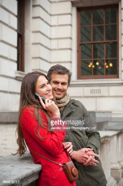 Couple talking on cell phone outside urban building