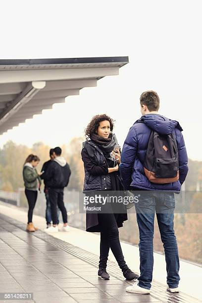 Couple talking on subway platform while friends standing in background