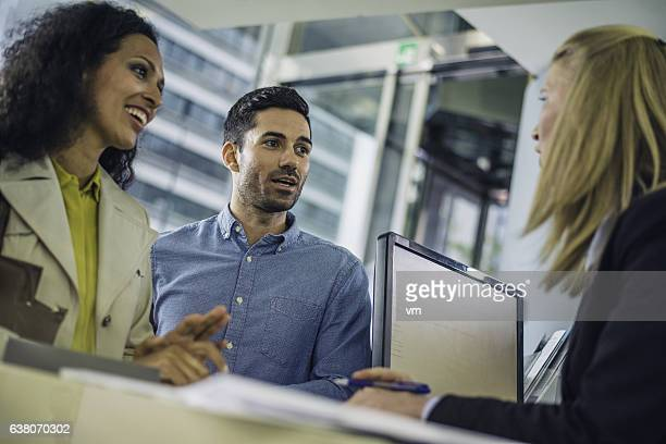 Couple talking to a bank teller