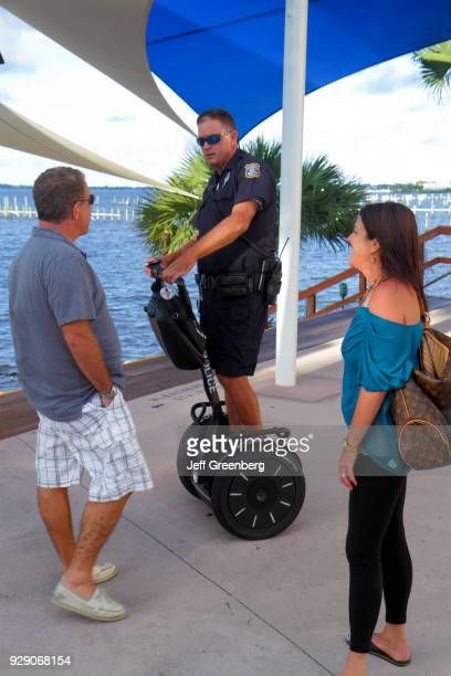Couple talking to a policeman riding a segway on Riverwalk Stage.