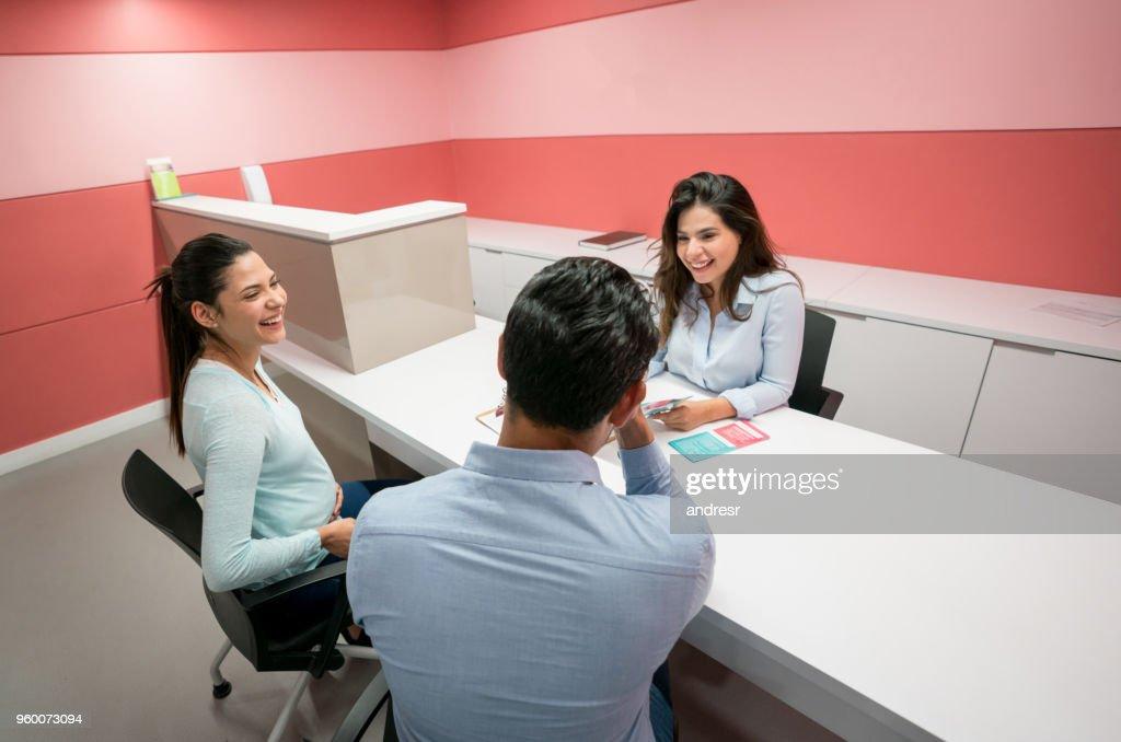 Paar im Gespräch mit administrativen Assistenten auf der Entbindungsstation suchen sehr glücklich : Stock-Foto
