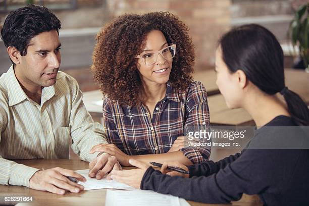 couple talking to bank manager - interracial wife photos stock photos and pictures