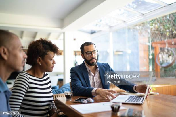 couple talking to finance advisor at home - customer stock pictures, royalty-free photos & images