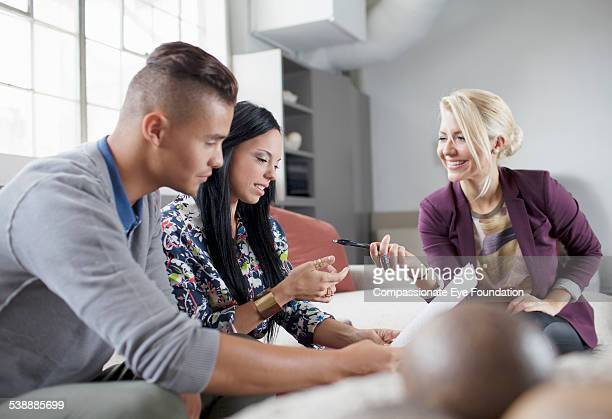 """couple talking to financial adviser in living room - """"compassionate eye"""" stock pictures, royalty-free photos & images"""
