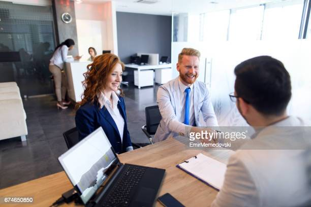 couple talking to loan officer and shaking hands - mortgage stock pictures, royalty-free photos & images