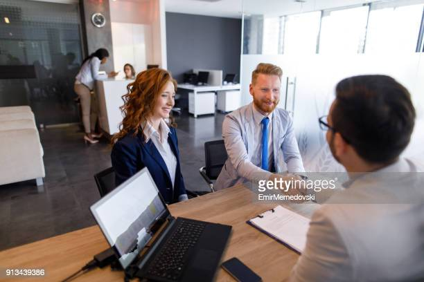 couple talking to loan officer and shaking hands - bank manager stock pictures, royalty-free photos & images