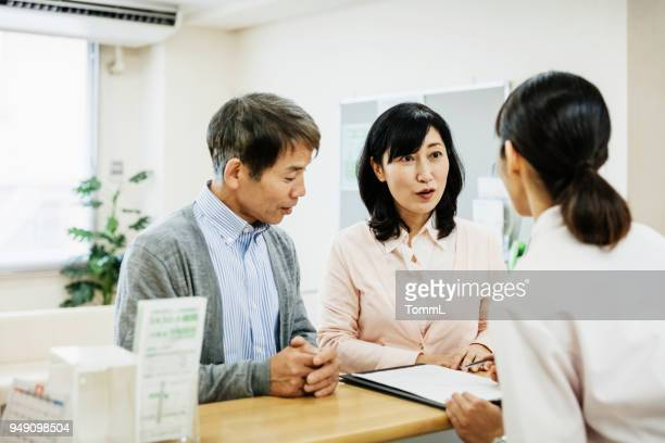 couple talking to nurse and filling out forms at hospital - medical receptionist uniforms stock photos and pictures