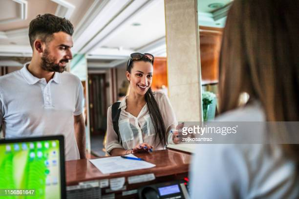 couple talking to receptionist at hotel lobby - guest stock pictures, royalty-free photos & images