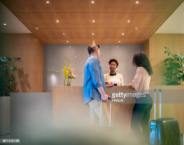 couple talking to receptionist at hotel lobby - hotel lobby stock pictures, royalty-free photos & images