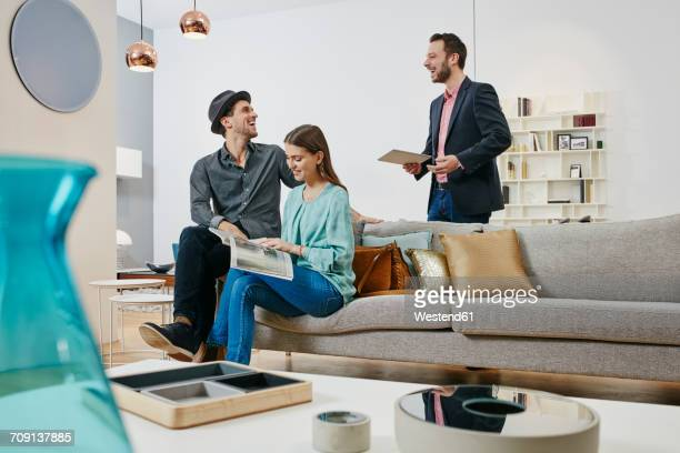 Couple talking to salesman in furniture store