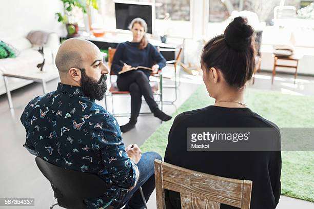 Couple talking to woman taking notes