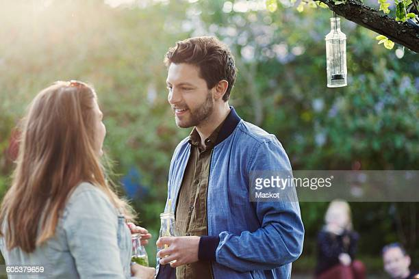 couple talking while holding drink bottles at summer party - 向かい合わせ ストックフォトと画像