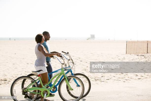 couple talking while pushing bikes on beach - santa monica stock pictures, royalty-free photos & images