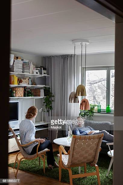 Couple talking while relaxing in living room at home