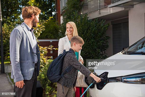 couple talking while their son plugs in renault zoe - electric vehicle charging station stock photos and pictures