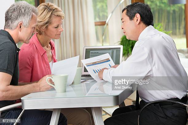 Couple talking with financial advisor at table