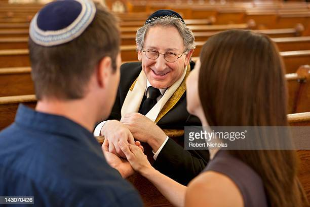 couple talking with rabbi in synagogue - rabbi stock pictures, royalty-free photos & images
