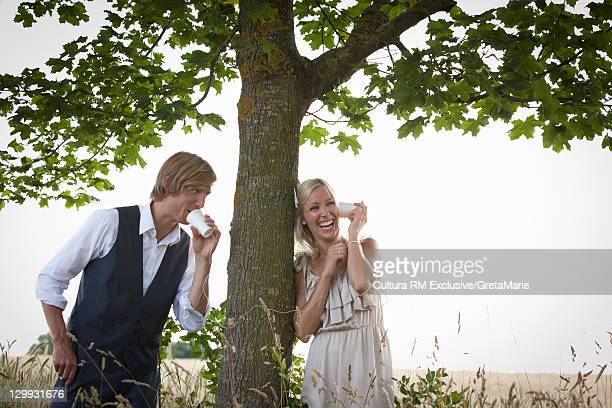 Couple talking with tin can telephone