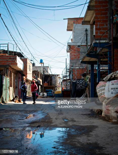 Couple talks on an alley at the Padre Carlos Mugica neighborhood, also known as Villa 31 shantytown, in Buenos Aires, on July 25 amid a lockdown...