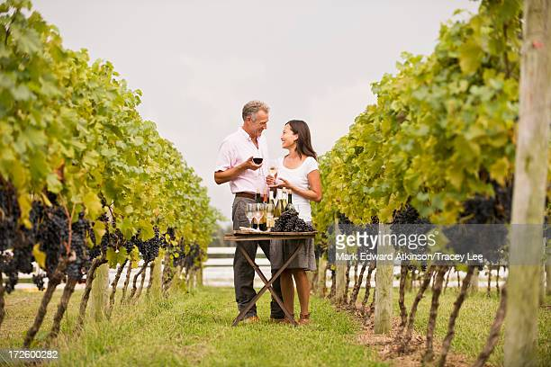 Couple tasting wine together in vineyard