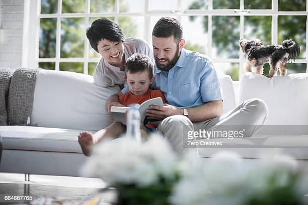 Couple teaching son to read book on sofa
